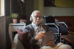 Elderly man streaming netflix on a tablet